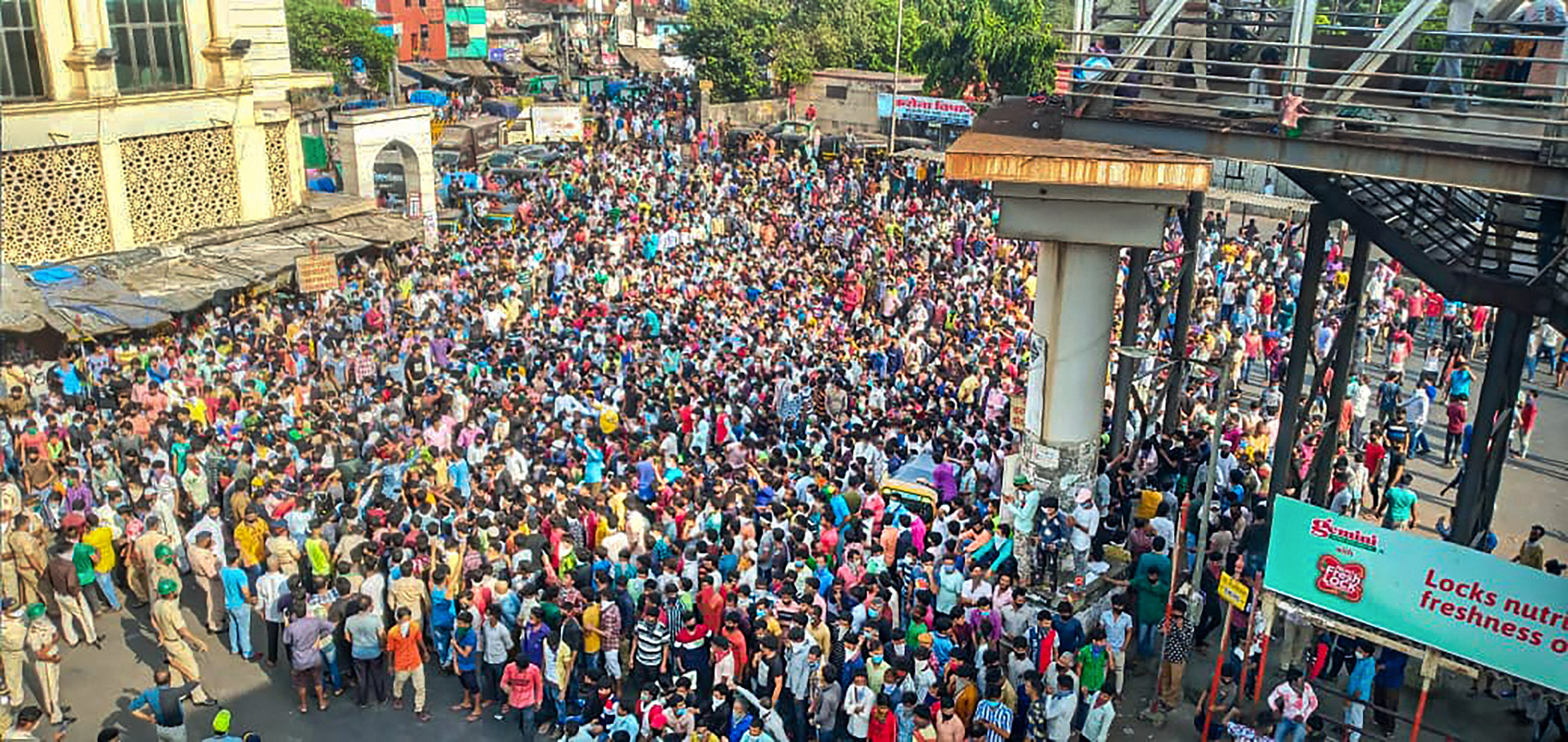 Migrant workers gather outside Bandra West Railway Station as they defy lockdown norms and request to leave for their native places after PM Narendra Modi announced the extension of nationwide lockdown till May 3 in the wake of coronavirus pandemic, in Mumbai, Tuesday, April 14, 2020.