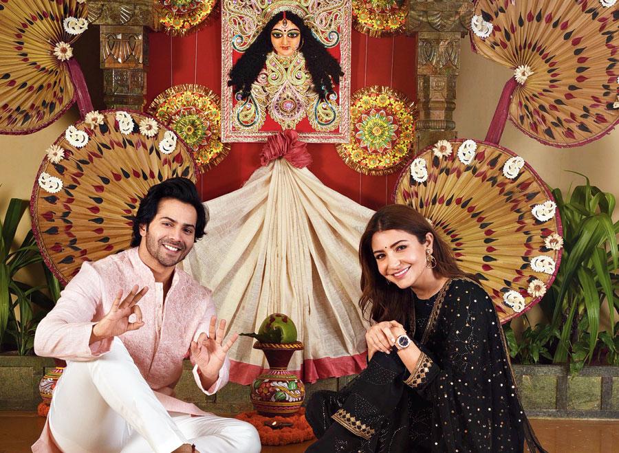 Varun Dhawan and Anushka Sharma pose in front of a makeshift puja mandap at The Oberoi Grand