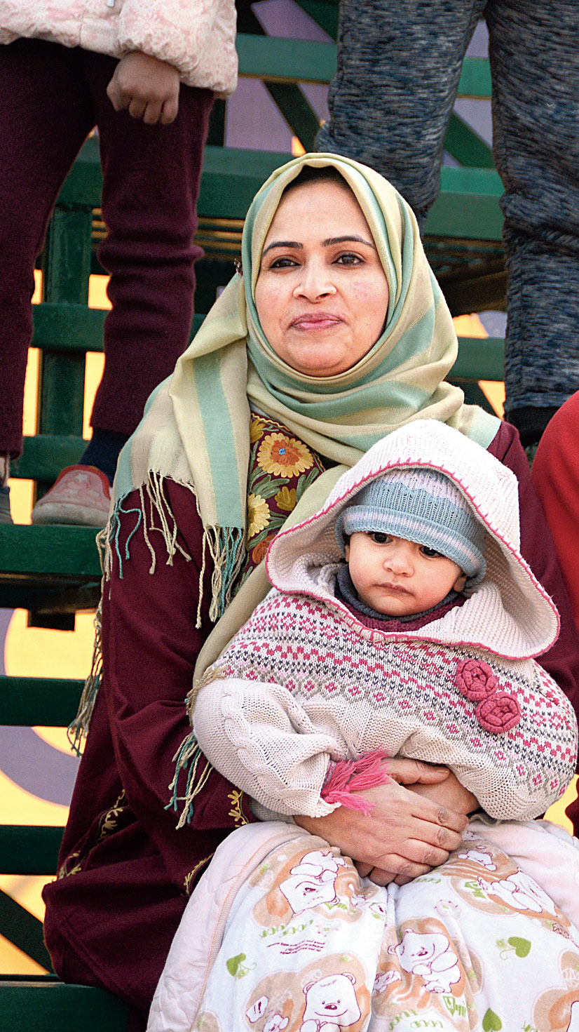 A Real Kashmir FC fan and her daughter watch the match