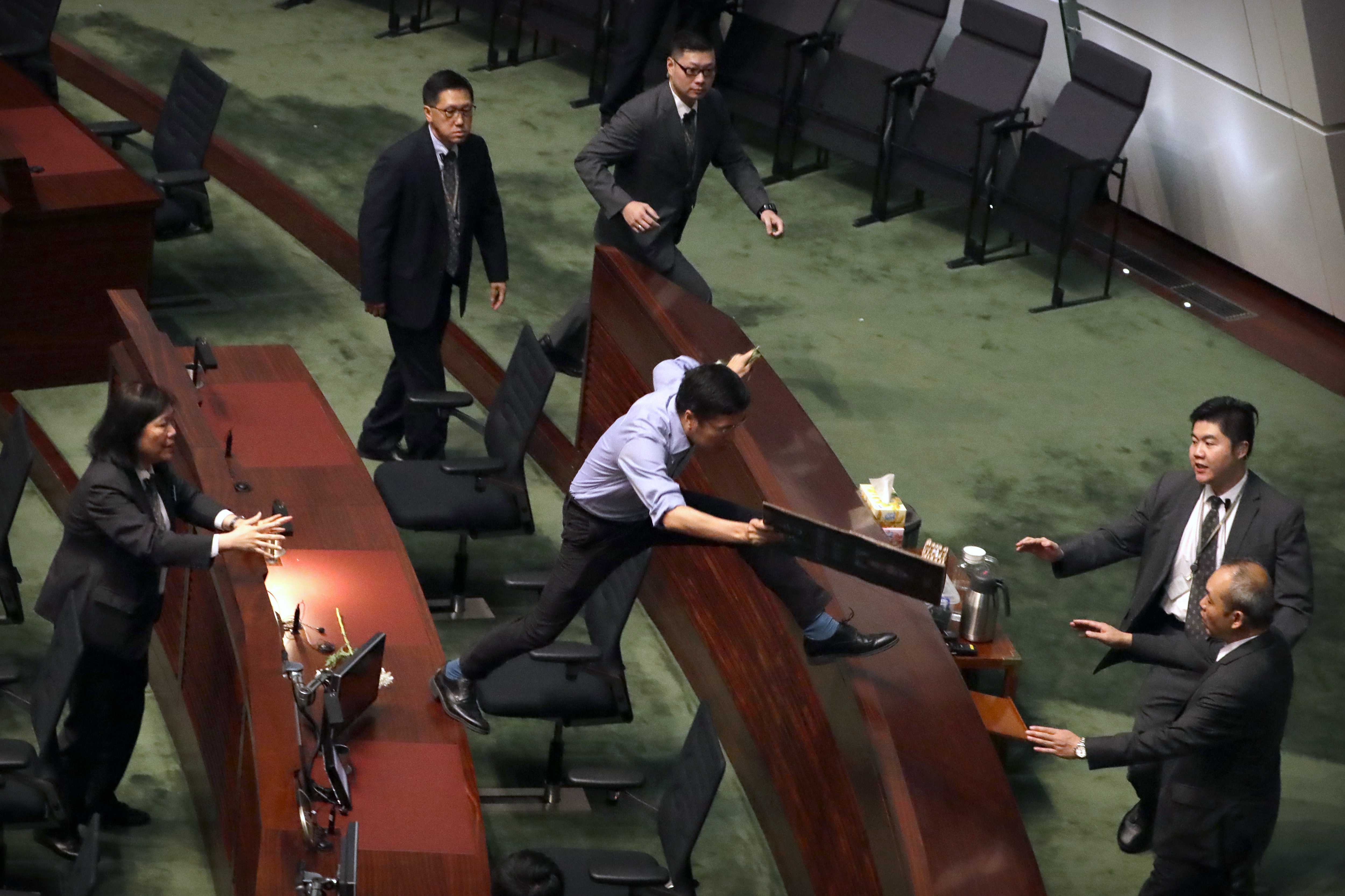 Security officers pursue Au Nok-hin, center, as he leaps across desks to chase Carrie Lam as Lam leaves a QandA session with lawmakers at the Legislative Council in Hong Kong on October 17, 2019