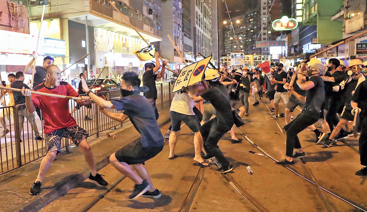 Protesters in black shirts fight a group of men with poles in Hong Kong on Monday.
