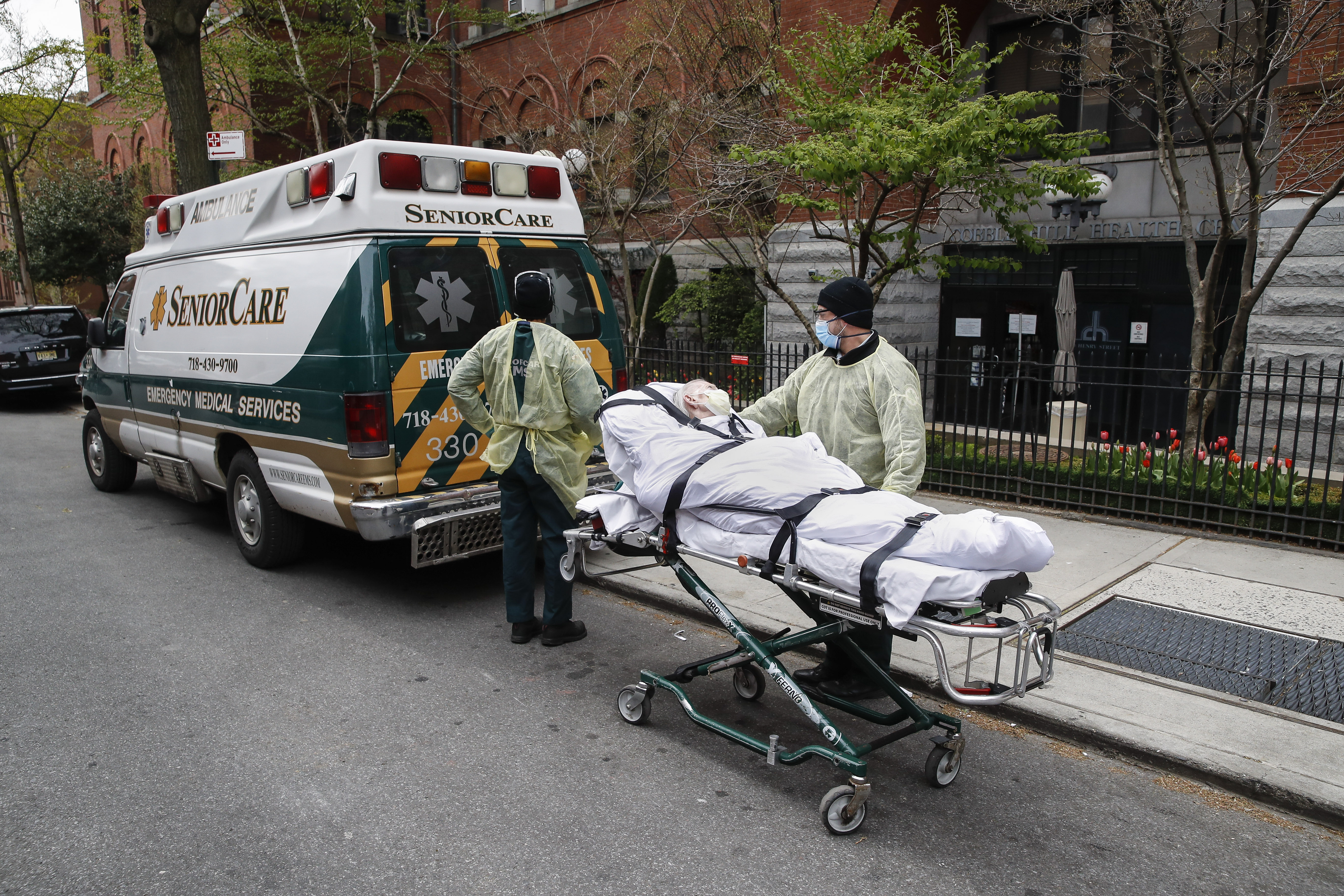 A patient is wheeled out of Cobble Hill Health Center by emergency medical workers
