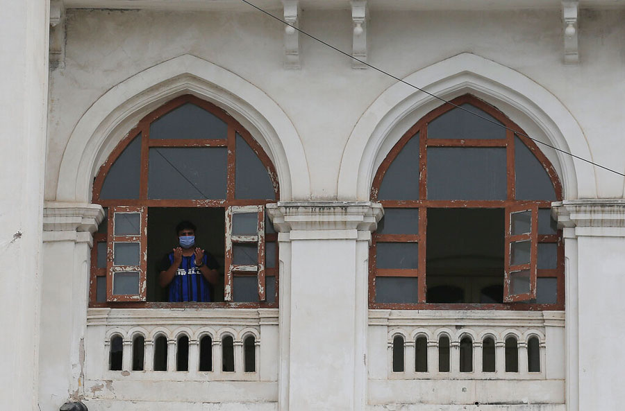 A Muslim offers prayers standing by a window of the Charminar Unani Hospital, currently used as a quarantine center, in Hyderabad on Friday