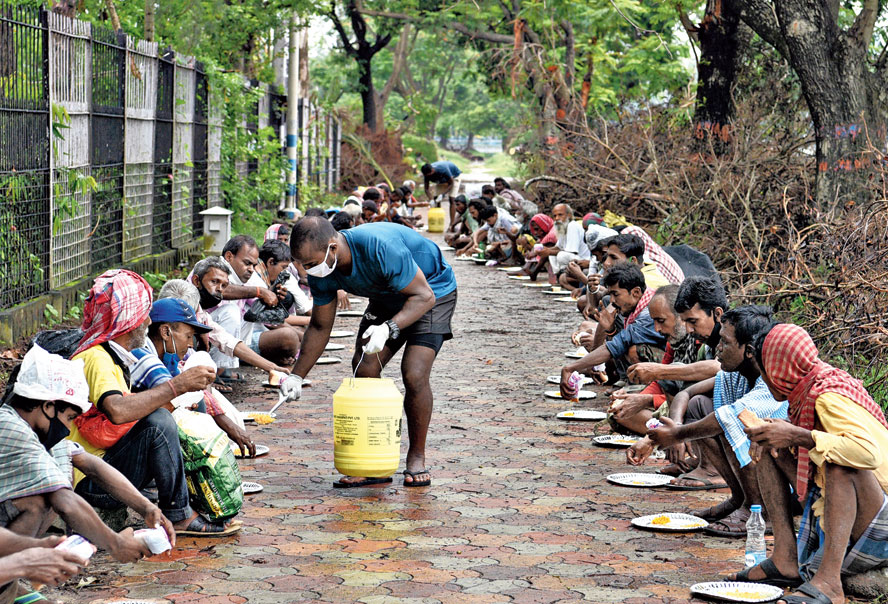 Shailen Tudu serves food to a group near Mohammedan Sporting Club on Tuesday.