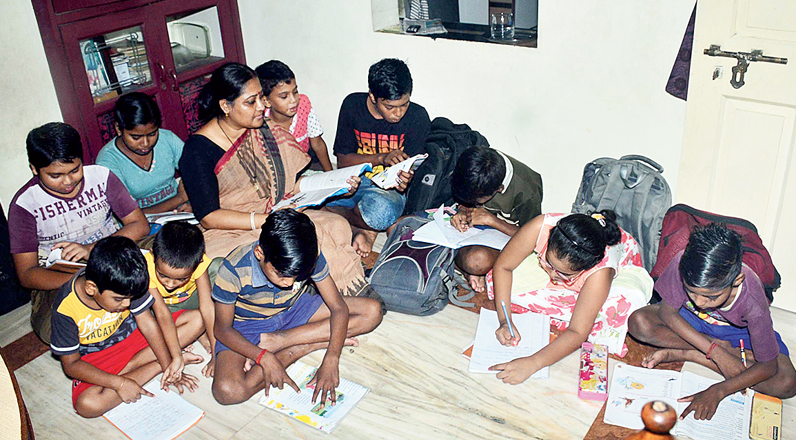 Rupa Chakraborty among students in her dining space.