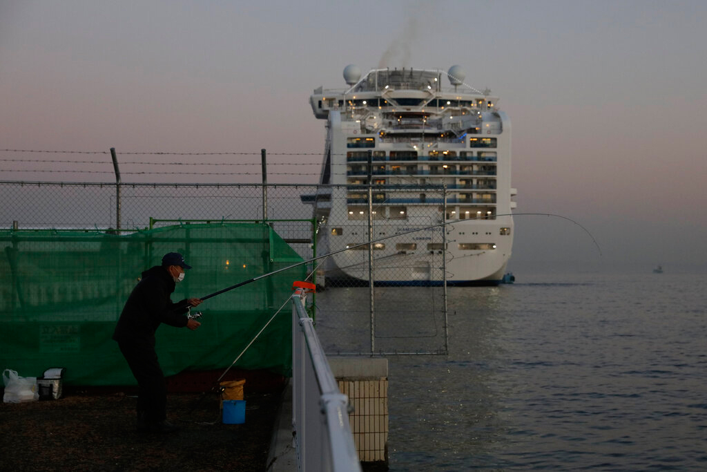 A man fishes behind the quarantined Diamond Princess on Thursday near Tokyo