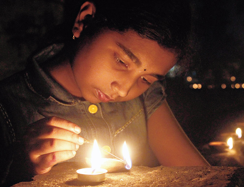 A girls lights diyas in Bhubaneswar on Tuesday evening.