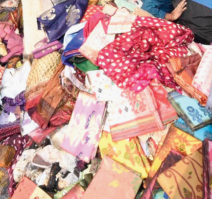 Saris recovered from the Adi Dhakeswari Bastralaya store by employees and heaped on the road in Gariahat.
