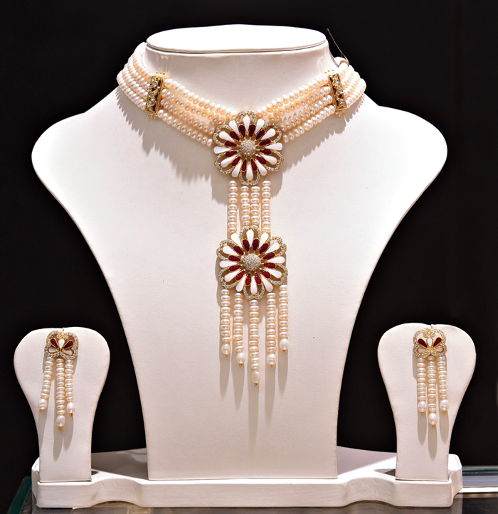 This choker set with a pair of earrings and bracelets, made of ivory freshwater pearls, spells elegance. The double pendants studded with cubic zircons on gold-polished silver alloy can be paired with a cocktail dress.  Rs 17,000 @ Chandrani Pearls