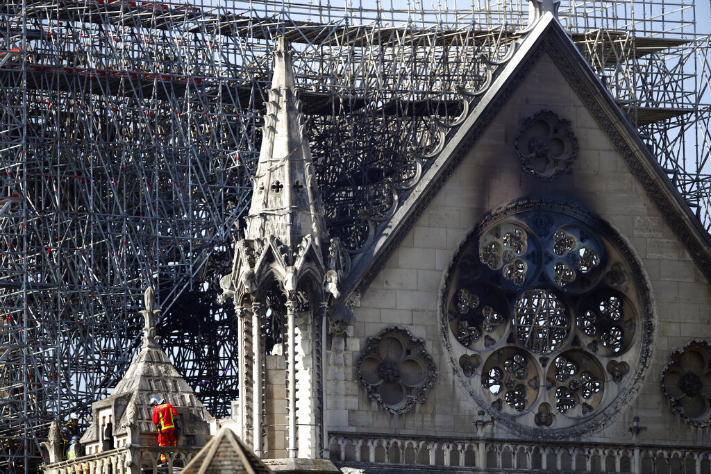 A fire fighter makes his way on a balcony of Notre Dame cathedral on Wednesday, April 17, 2019 in Paris.