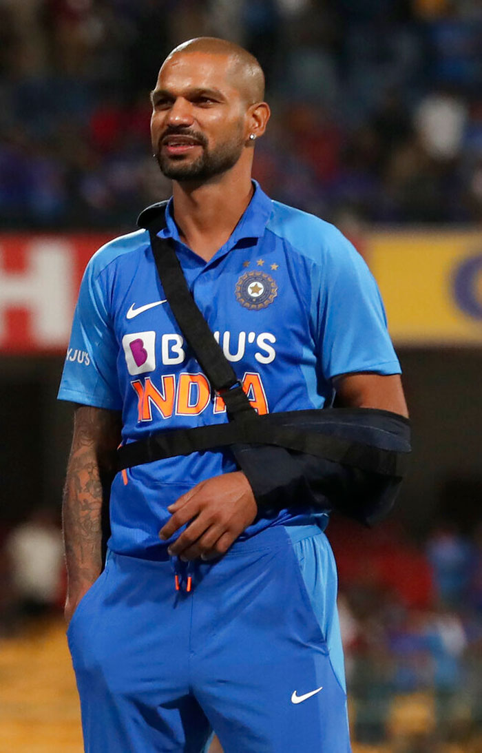 India's Shikhar Dhawan uses a sling to rest his arm during the presentation ceremony after their win in the third one-day international cricket match between India and Australia in Bangalore on Sunday