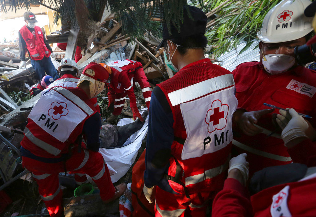 Members of the Indonesian Red Cross team carry the body of a tsunami victim in Palu, Indonesia.