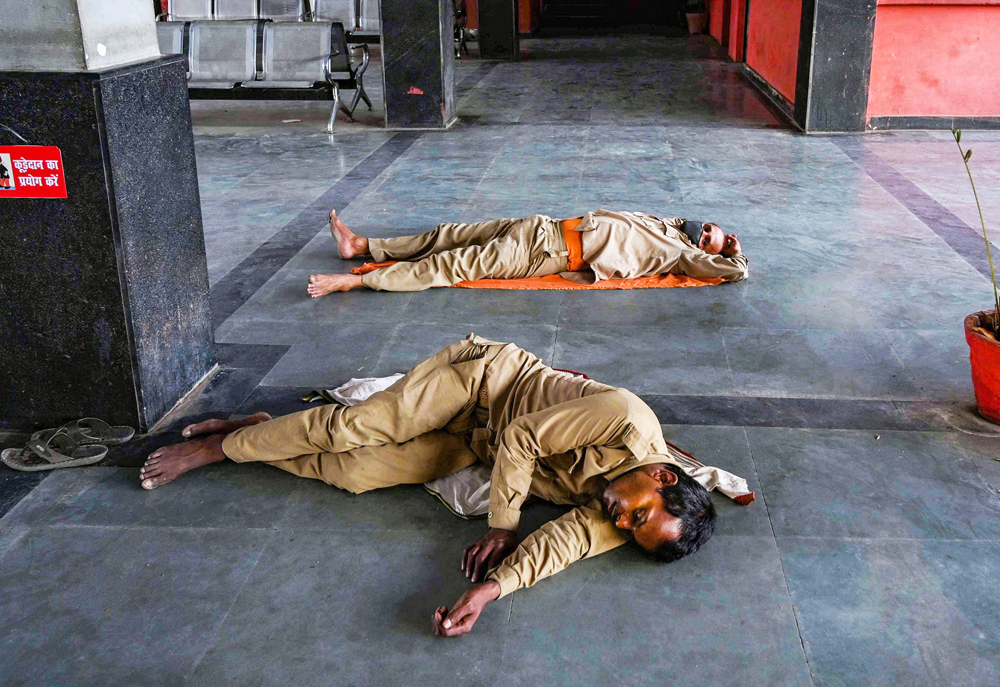 UPSRTC drivers sleep on the floor after bringing back stranded workers from Madhya Pradesh, during ongoing Covid-19 lockdown in Prayagraj, Thursday, April 30, 2020.