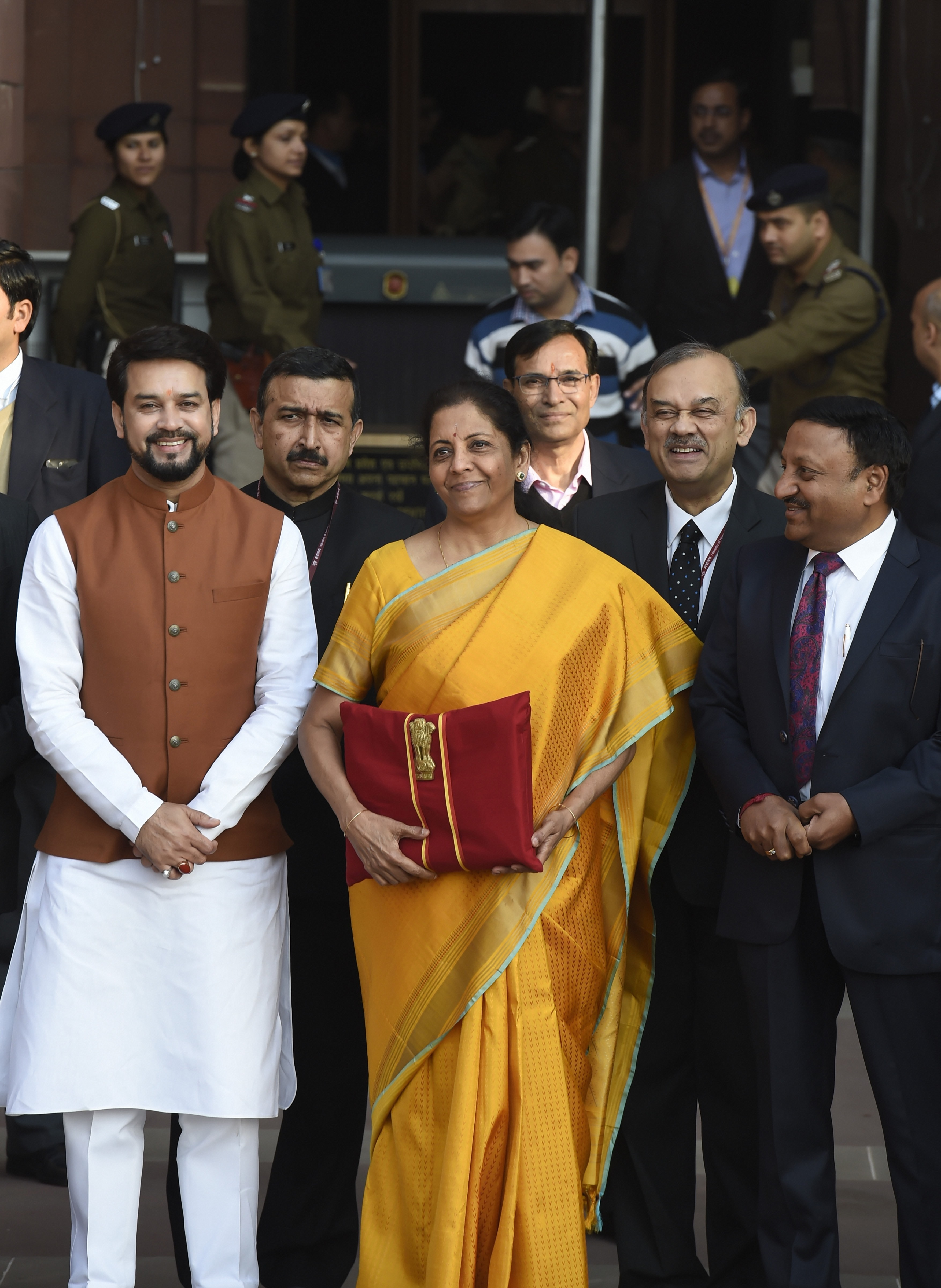 Union finance minister Nirmala Sitharaman, holding a folder containing the Union Budget documents, poses for photographers along with her deputy Anurag Thakur and a team of officials, outside the ministry of finance, North Block in New Delhi, Saturday, February 1, 2020.