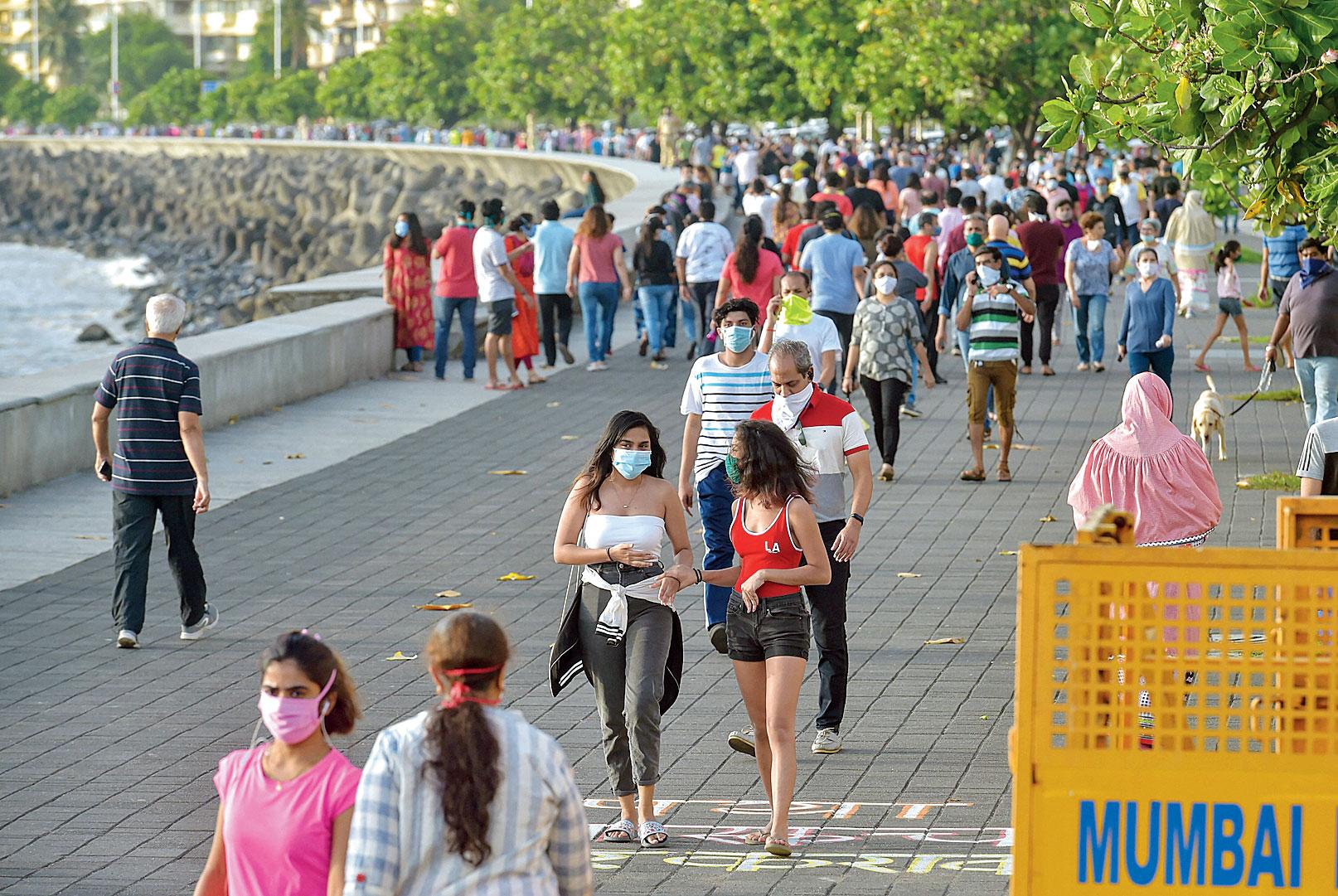 People walk along the promenade at Marine Drive in Mumbai on Sunday.