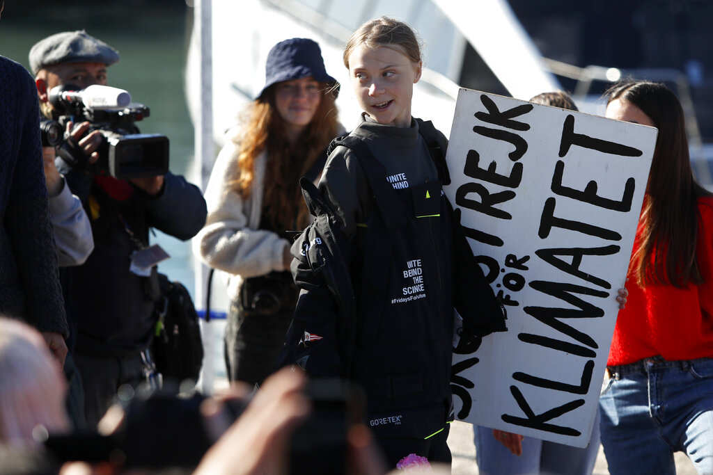 Climate activist Greta Thunberg holds a sign reading 'School strike for the climate' after arriving in Lisbon aboard the sailboat La Vagabonde Tuesday, December 3, 2019