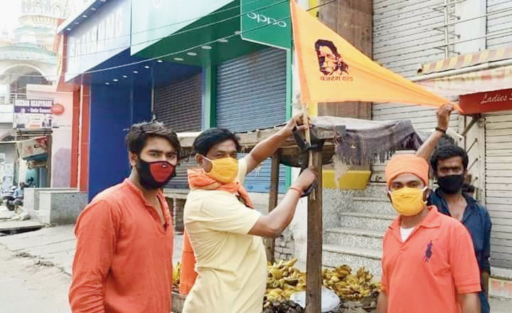 A saffron flag being tied to a shop in Nalanda.