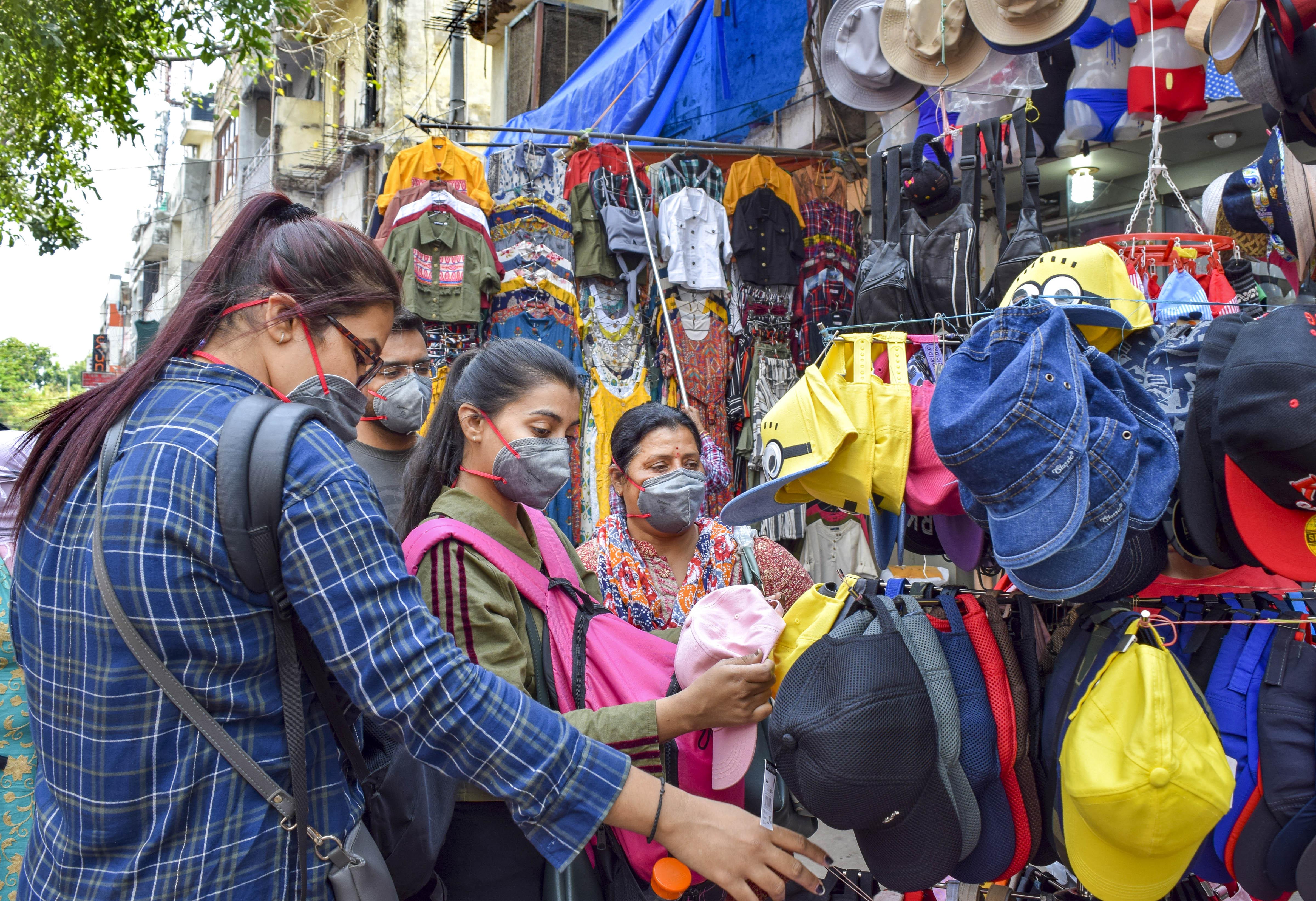 Customers wear protective mask in view of coronavirus pandemic, at Sarojini Nagar market in New Delhi, Sunday, March 15, 2020