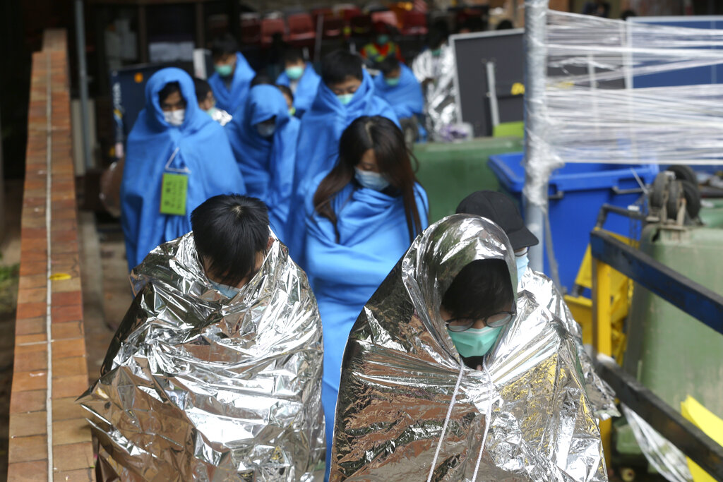 Injured protesters huddle under blankets as they walk at the Polytechnic University in Hong Kong, Tuesday, November 19, 2019.