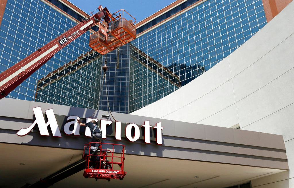 In this Tuesday, April 30, 2013, file photo, a man works on a new Marriott sign in front of the former Peabody Hotel in Little Rock, Arkansas.