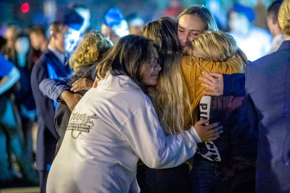 People hug each other during a vigil for the Saugus High School shooting victims on November 14 in Santa Clarita, California