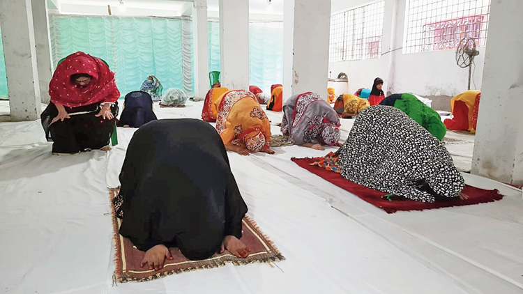 Women offer namaz at Harinkhola near Arambagh on Monday.