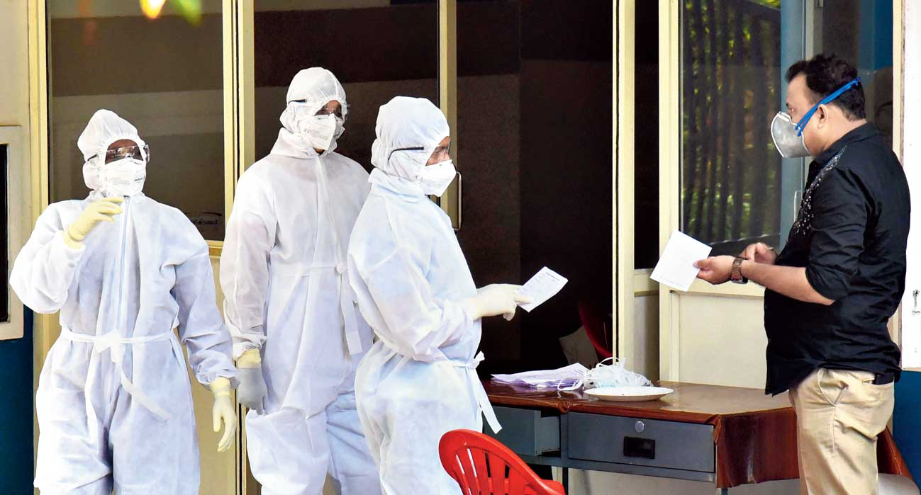 Medical staff wear masks and protective suits to mitigate the spread of the coronavirus outside the special isolation ward of a hospital in Kochi on Thursday.