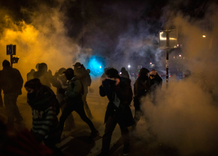 Protesters run away from tear gas in Paris on December 5