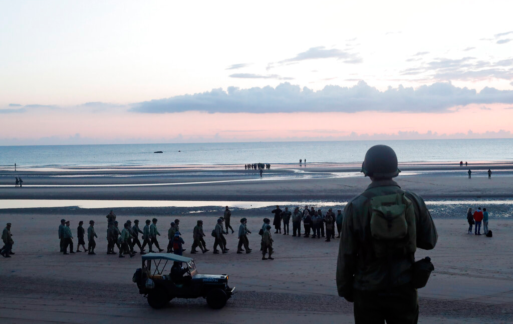 A World War II re-enactor looks out over Omaha Beach, in Normandy, France, at dawn on Thursday, June 6, 2019 during commemorations of the 75th anniversary of D-Day.