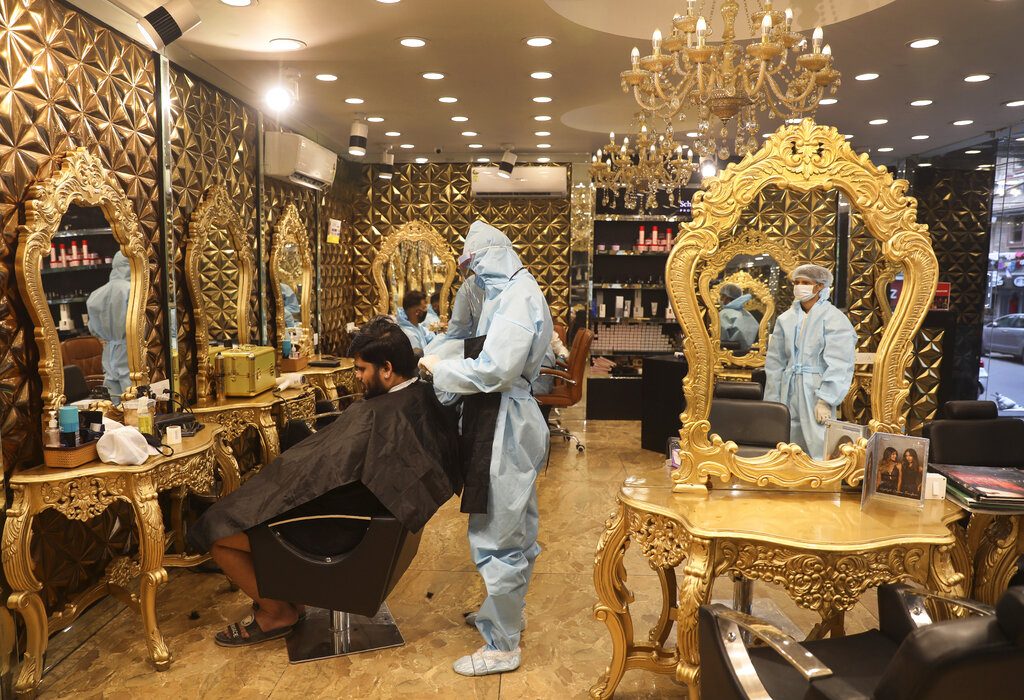 A hairdresser in personal protective suit attends to a customer at a hair salon in New Delhi, on Friday, June 5, 2020