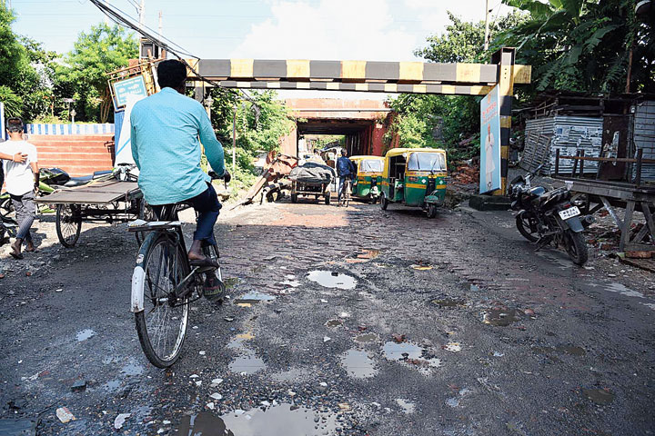 The battered road that leads to Noapara Metro station.