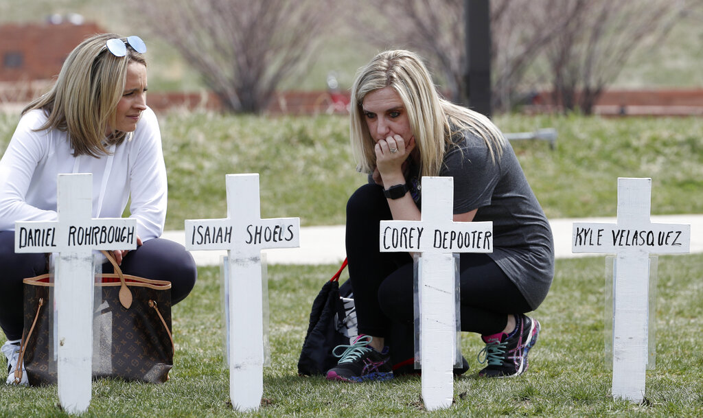Cassandra Sandusky, right, a graduate of Columbine High School, pauses with her friend, Jennifer Dunmore, at a row of crosses bearing the names of the victims of the attack at the school 20 years ago on Saturday, April 20, 2019