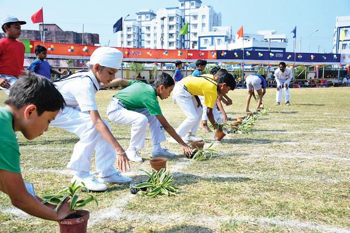 Students plant saplings in the hurdle race in Haldia on Saturday