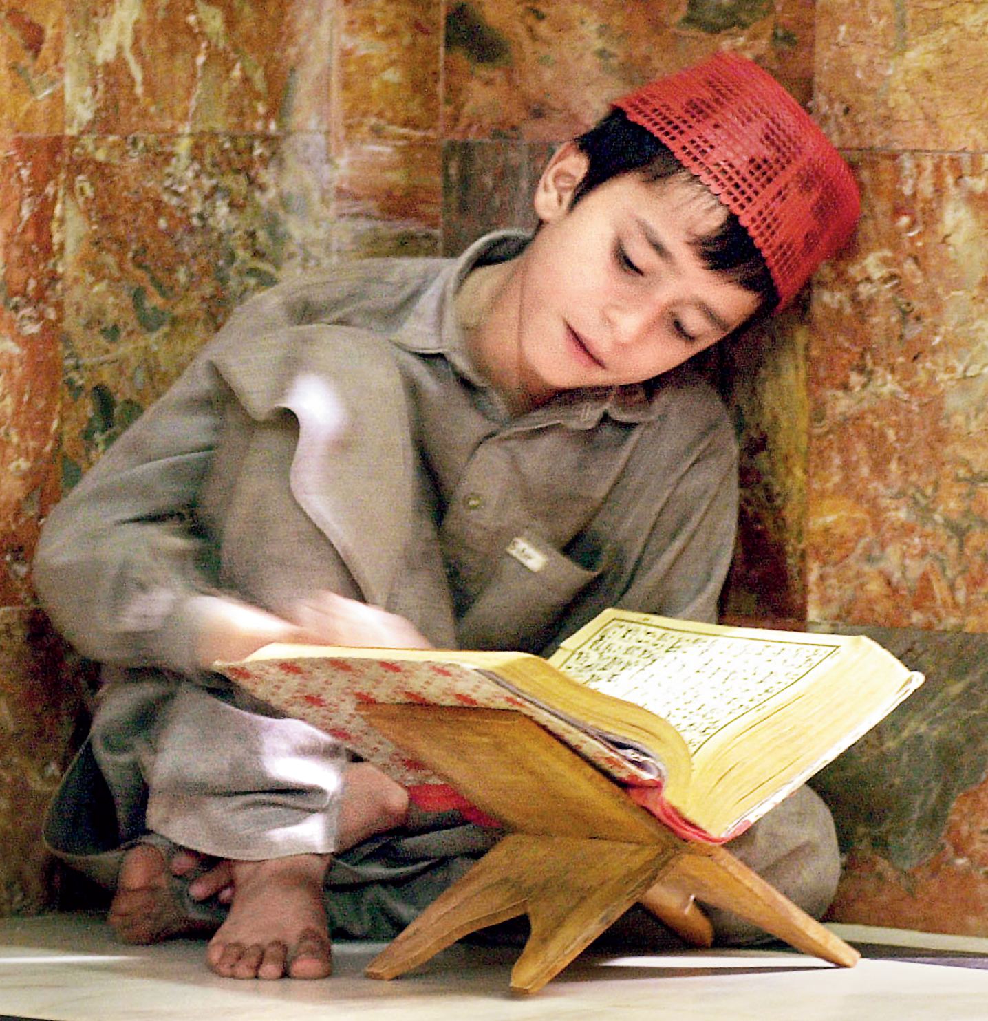 A boy in solitary study of the Koran at the Mohabat Khan Mosque in Peshawar, Pakistan near the Afghanistan border