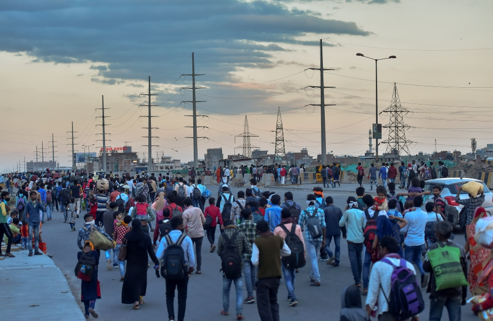 A group of migrant workers walk to their native places amid the nationwide complete lockdown, on the NH24 near Delhi-UP border in New Delhi