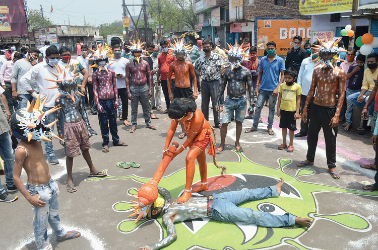 Hanuman to the rescue: A boy dressed up as Lord Hanuman hits another dressed as the novel coronavirus at a programme organised by the district administration involving the local youth of Katras Mor at Jharia in Dhanbad on Friday.
