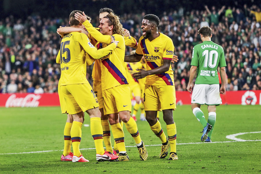 Barcelona's Clement Lenglet (left) celebrates with teammates after scoring the third goal against Real Betis during the La Liga match at the Benito Villamarin Stadium in Seville on Sunday.