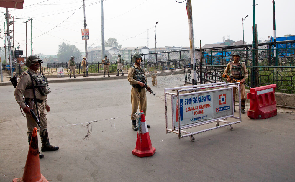 Paramilitary soldiers stand guard near a temporary barricade during restrictions in Srinagar on Friday