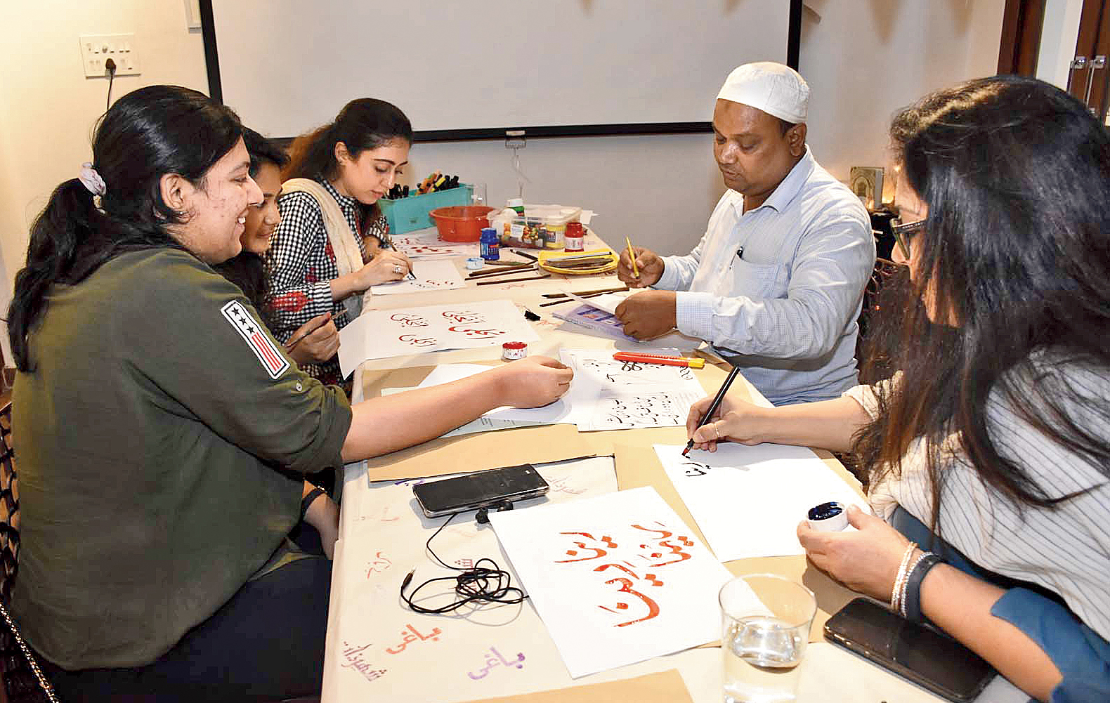 Urdu calligraphy artist Usman Ghani teaches students some fonts at a workshop in Art Rickshaw in Hindustan Park.