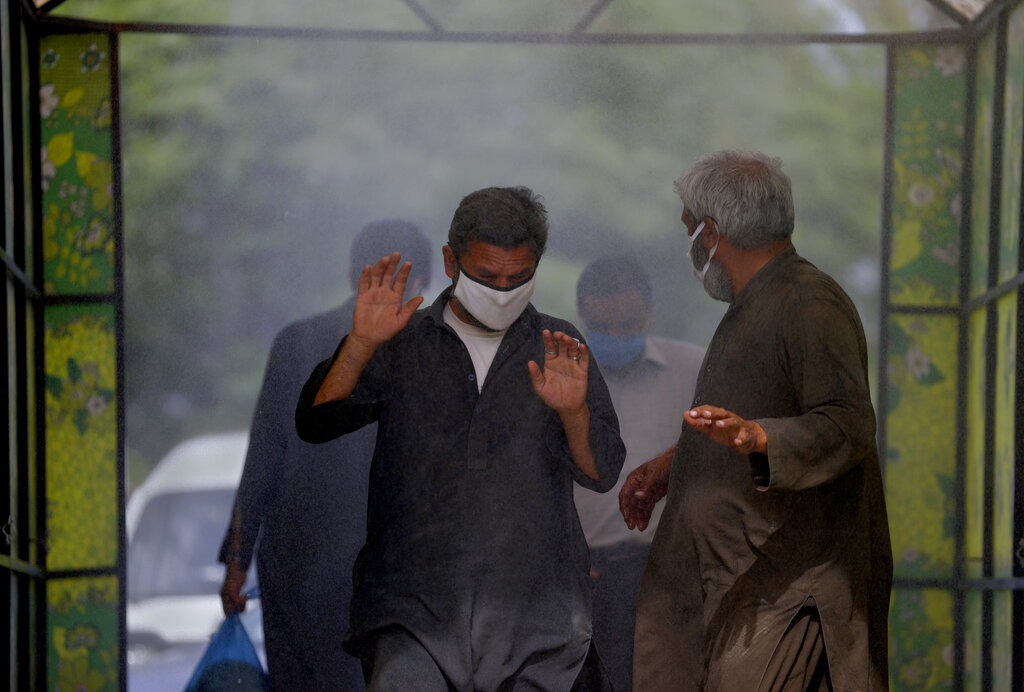 People walk through a disinfecting tunnel setup at an entrance to a wholesale vegetable and fruit market to help curb the spread of the coronavirus, in Islamabad, Pakistan, Monday, April 6, 2020.