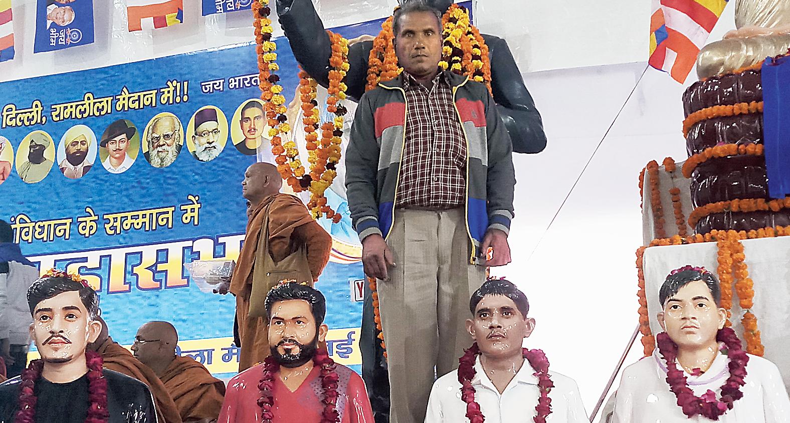 Suresh Kumar stands behind his son Amresh's bust (third from left) at the Ramlila Maidan on Sunday.