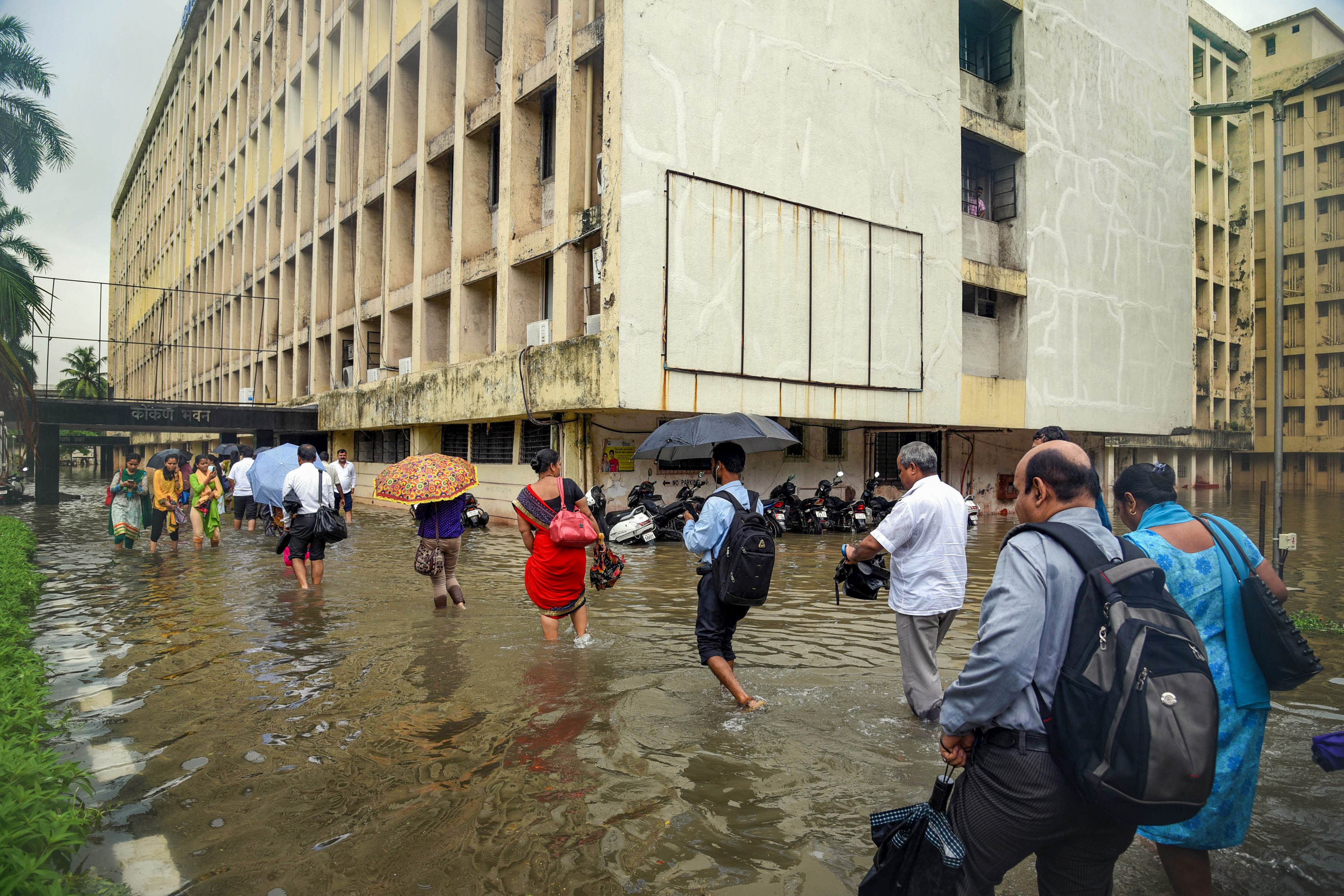 People make their way to the waterlogged Konkan Bhavan in Navi Mumbai that houses government offices after heavy rain on July 1.