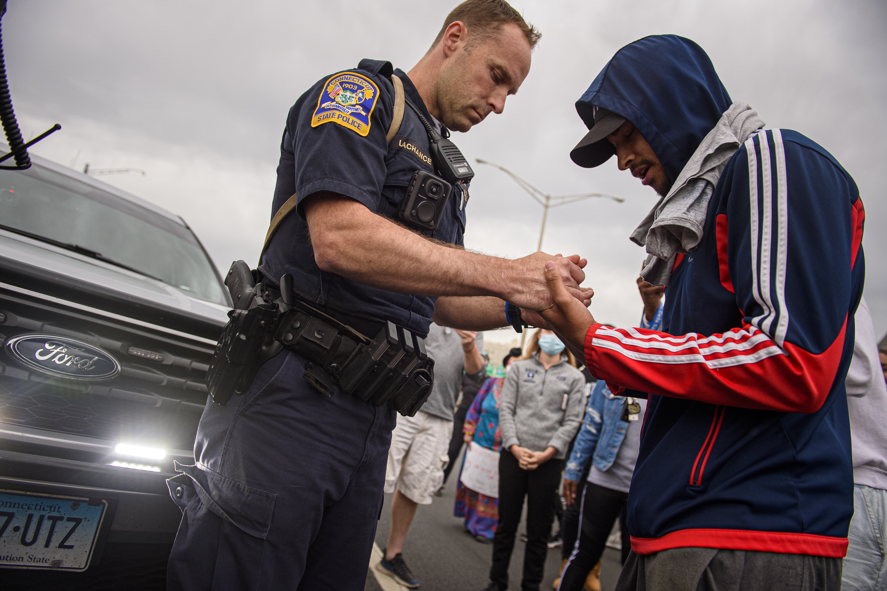 A Connecticut State Trooper prays with Nathaniel Swift, right, in the middle of Interstate 84 after it was closed down by hundreds protesting the death of George Floyd