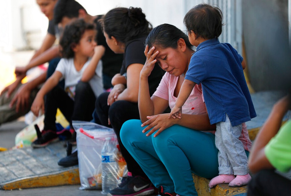 In this July 16, 2019, file photo, migrants wait at an immigration center on the International Bridge 1, in Nuevo Laredo, Mexico. In August 2019, the US put in place a regulation that would allow the authorities to indefinitely detain those who illegally cross the border