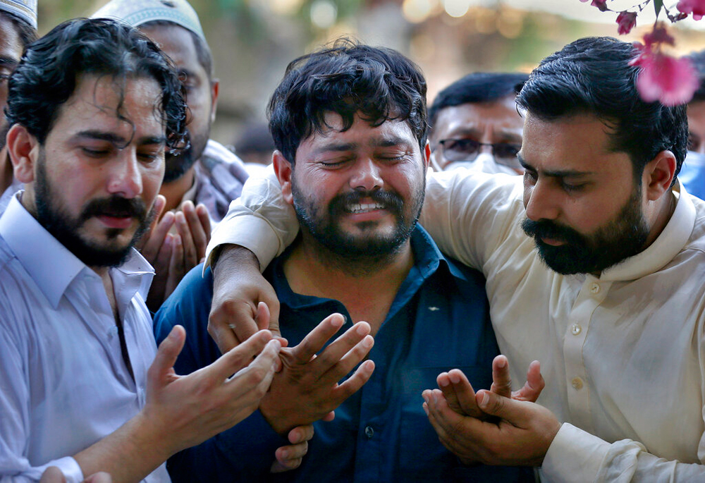 Relatives of Raja Fayyaz, who died in the plane crash in Karachi, mourn during a funeral in Rawalpindi on Monday