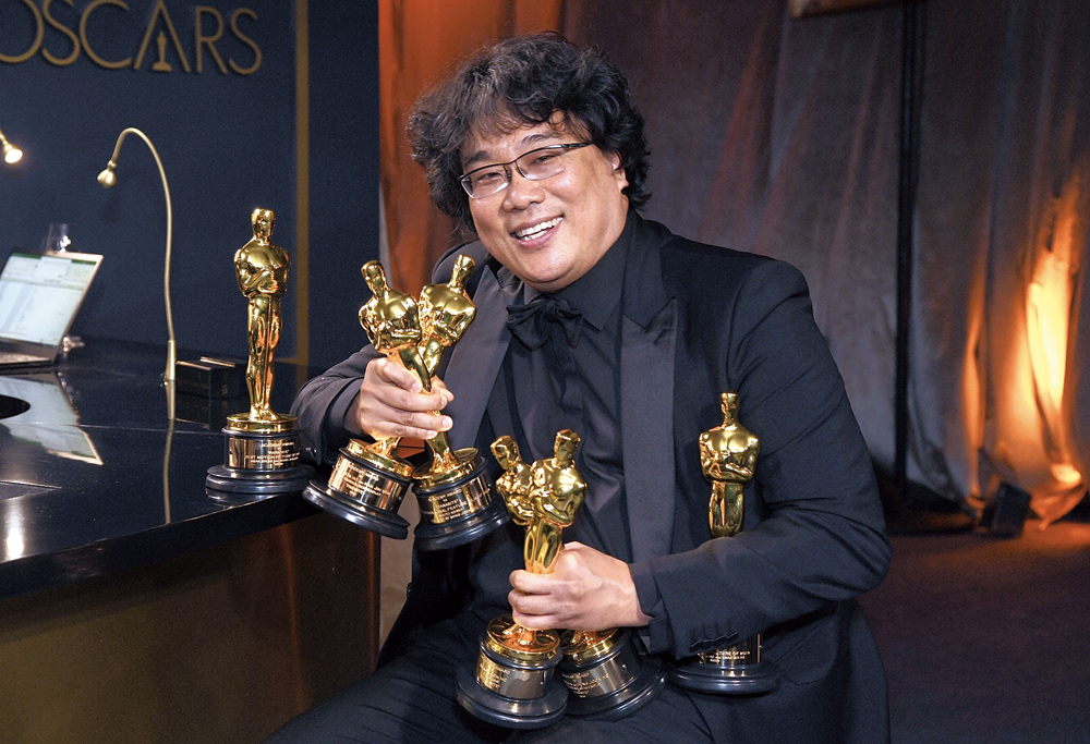 Bong Joon Ho poses with the Oscar trophies his film 'Parasite' received