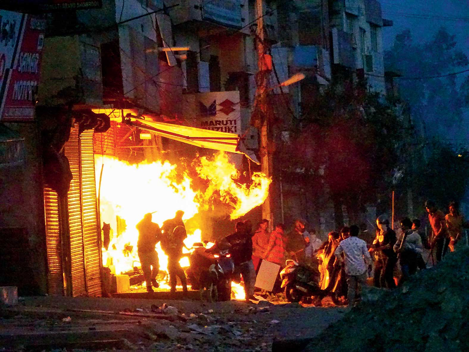 Rioters set ablaze a shop in northeast Delhi on Tuesday.