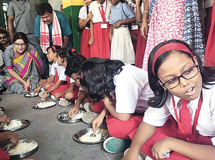 Locket Chatterjee with students having midday meals on Monday.