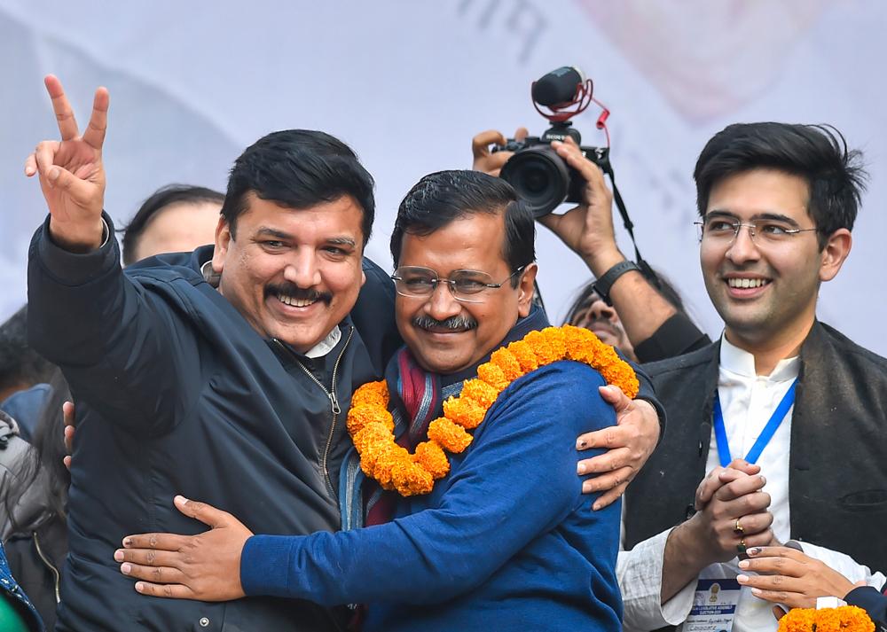 Arvind Kejriwal hugs party leader Sanjay Singh at the AAP office in New Delhi.