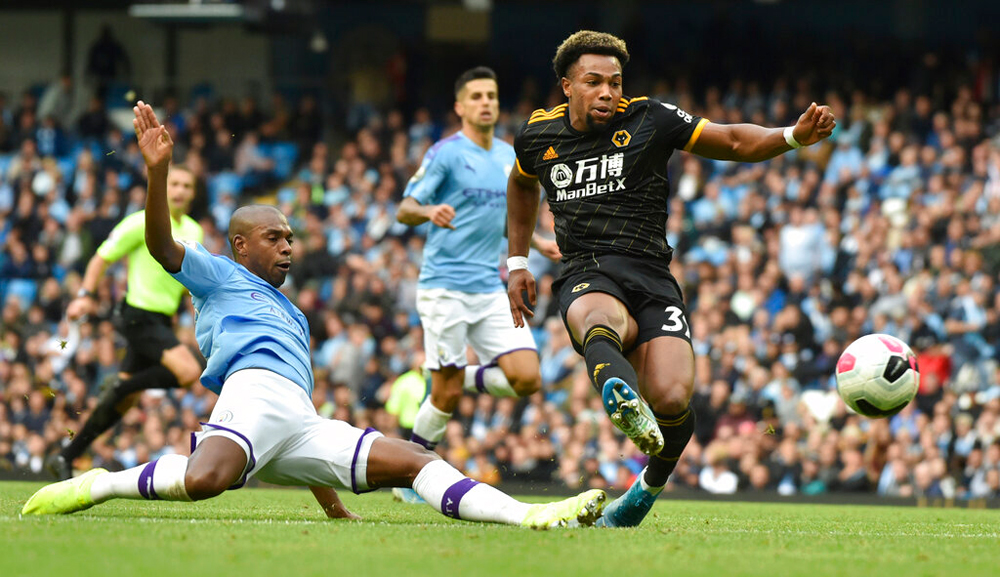 Wolverhampton Wanderers' Adama Traore, right, scores his second goal during the English Premier League soccer match between Manchester City and Wolverhampton Wanderers at Etihad stadium in Manchester, England, Sunday, October 6, 2019.